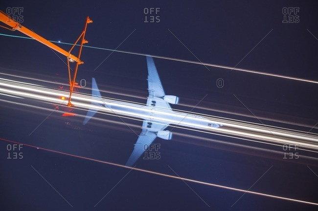 Low angle view of signal mast against light trails and airplane in sky at night