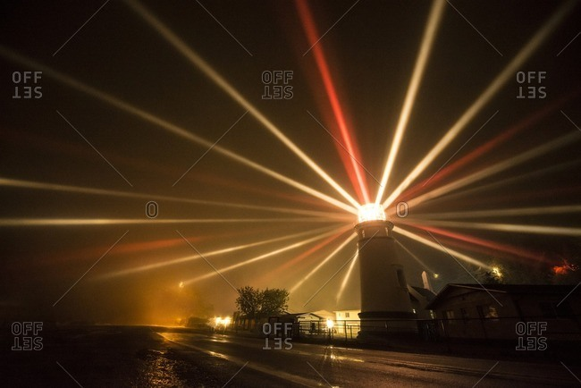 Light beams emitting from lighthouse by sea at night