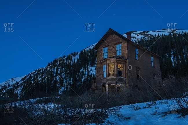 Low angle view of house on snow covered landscape against clear blue sky