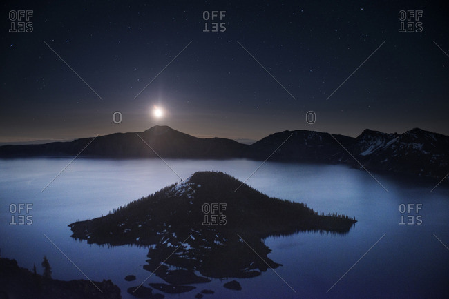 Scenic view of Wizard island in crater lake against sky at night