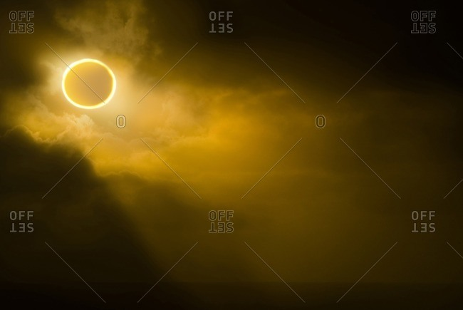 Low angle view of solar eclipse in sky during foggy weather