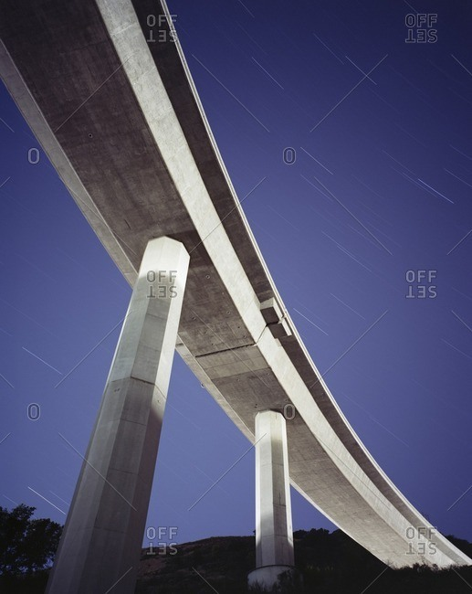 Low angle view of overpass against star trails at night