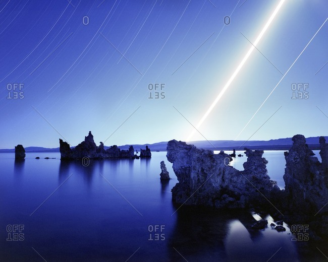 Rock formations in lake against star trails at night
