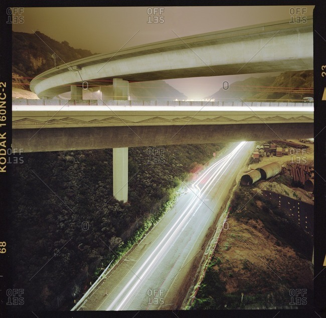 Lights trails on overpass by mountain during sunset