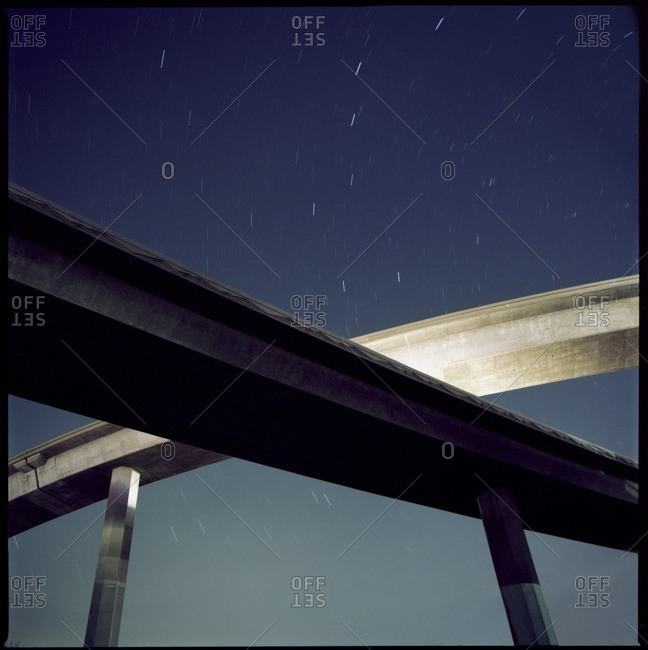 Low angle view of overpass against star trails