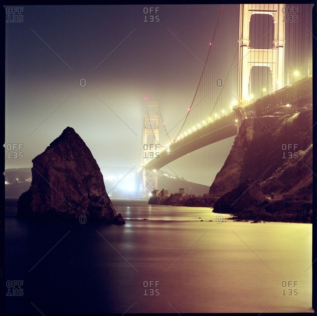 Low angle view of illuminated Golden Gate Bridge over bay during foggy weather