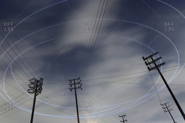 Low angle view of light trails over electricity pylons