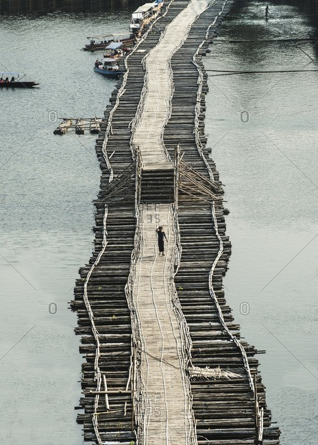 Thailand - December 5, 2013: Distant view of man walking on footbridge amidst river