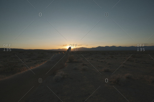 Optical illusion on person touching sun during sunset