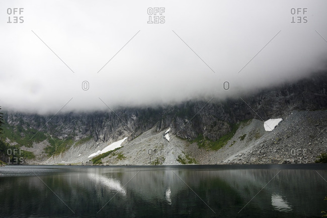 Scenic view of lake against mountain during foggy weather