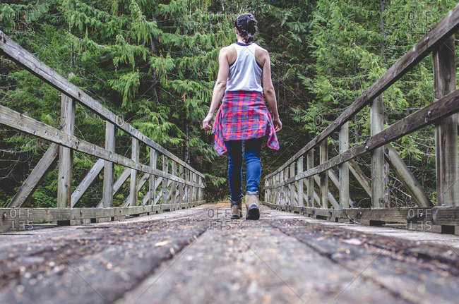 Rear view of woman walking on footbridge amidst trees in forest