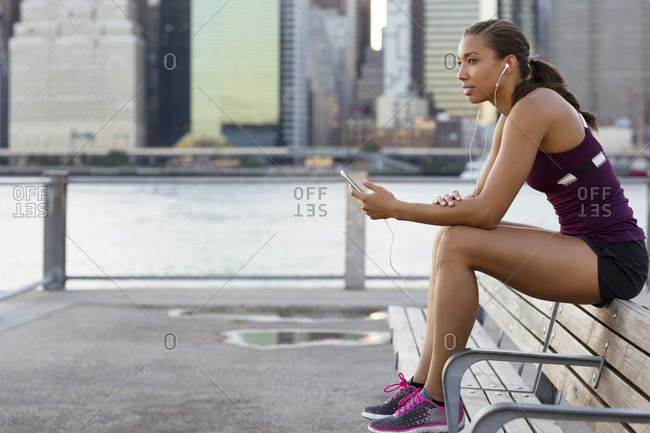 Athlete listening music while sitting on bench by river