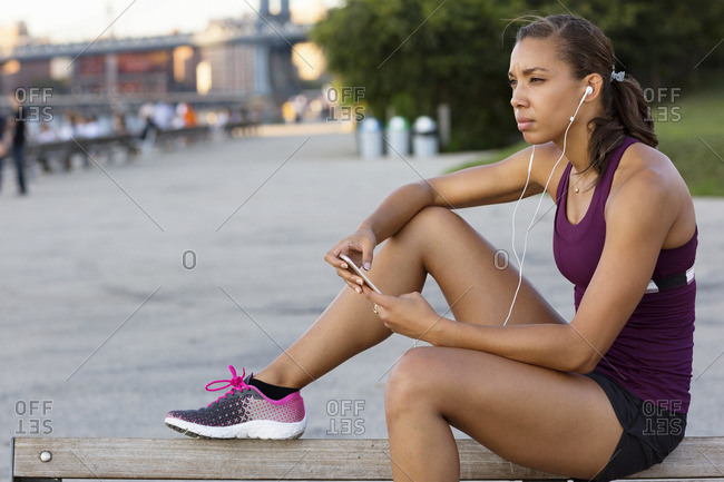 Athlete listening music while sitting on bench