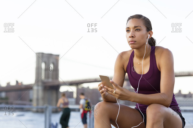 Thoughtful athlete listening music while sitting on bench
