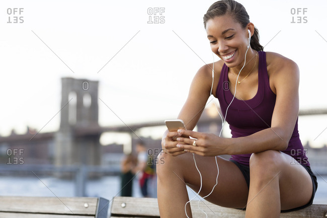 Happy athlete listening music while sitting on bench