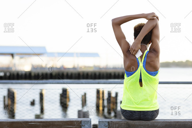 Rear view of athlete exercising while sitting on bench