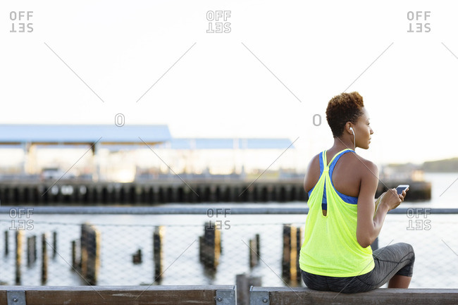 Rear view of athlete listening music while sitting on bench in city