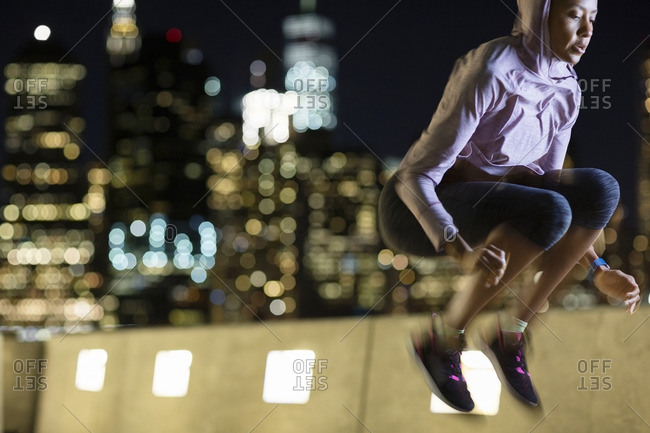 Athlete jumping in city at night