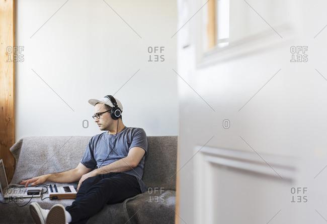 Man listening music while using laptop computer on sofa seen through doorway