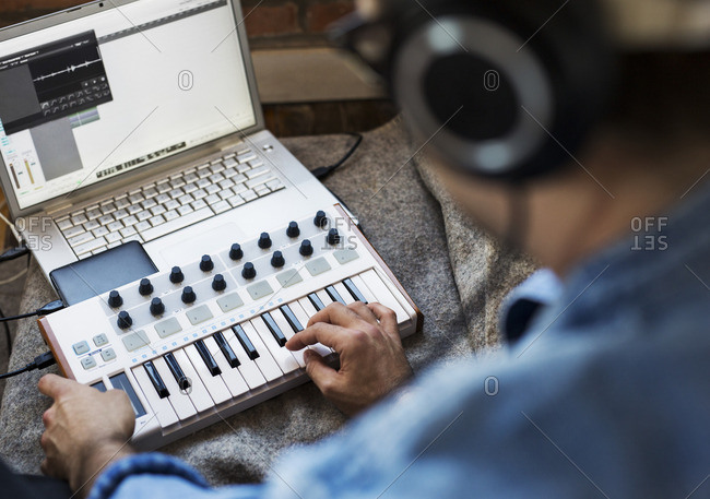 High angle view of man playing piano by laptop computer at home