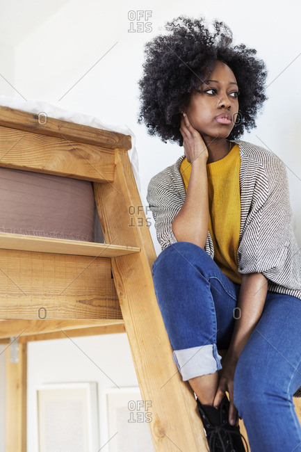 Woman looking away while sitting on ladder at home