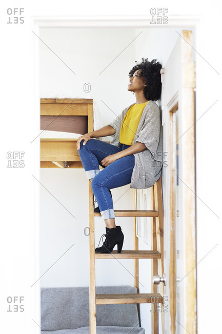 Woman looking up while sitting on bunkbed ladder seen through doorway