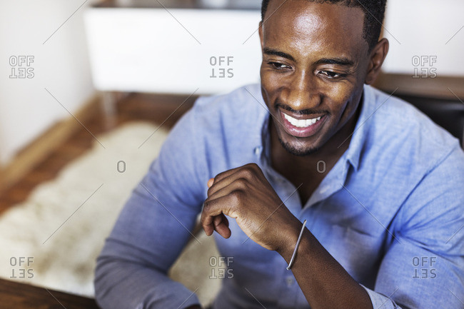 Happy man looking away while sitting at home