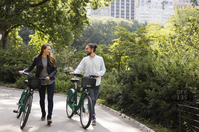 Couple talking while walking on footpath with bicycles