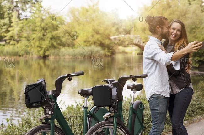 Man taking selfie while kissing girlfriend by lake