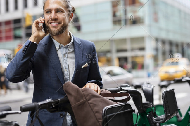 Businessman talking on mobile phone while standing at parking lot in city