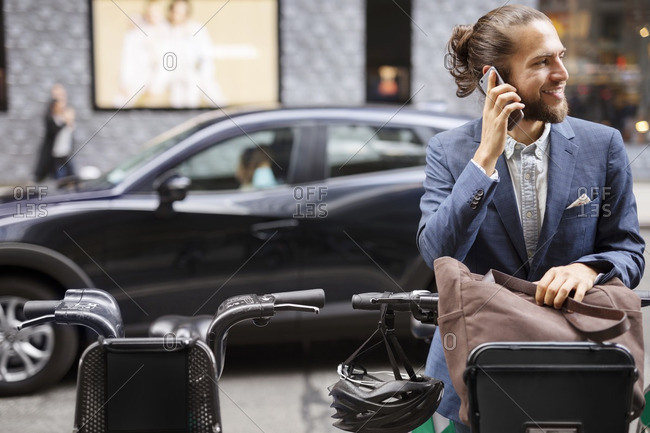 Businessman talking on mobile phone while standing at parking lot