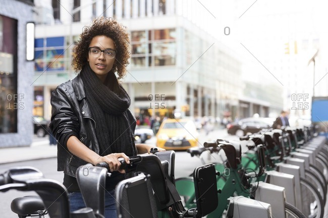 Woman looking away while standing by bicycle rack