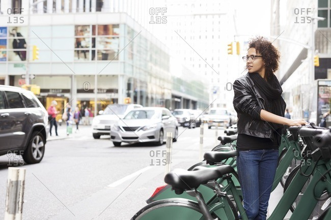 Woman looking away while standing by bicycle rack at parking lot