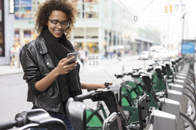 Happy woman using mobile phone while standing by bicycle rack