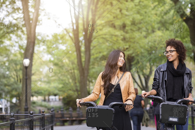 Friends talking while walking with bicycle on footpath