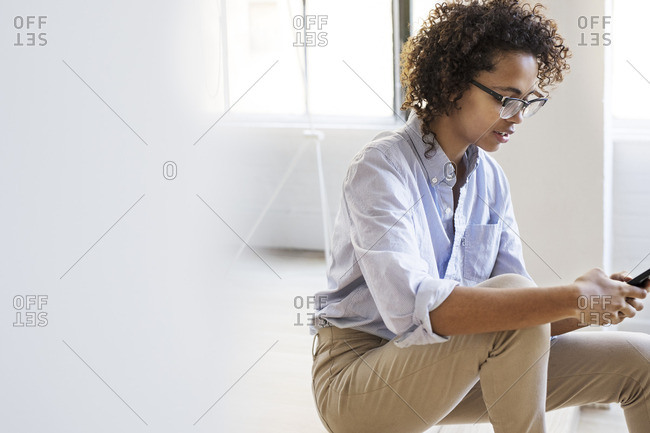 Businesswoman using mobile phone while sitting in lobby at office