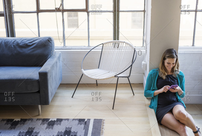 Smiling businesswoman using mobile phone while sitting in lobby at office