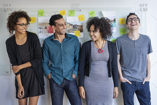 Multi-ethnic happy business people standing against whiteboard at office
