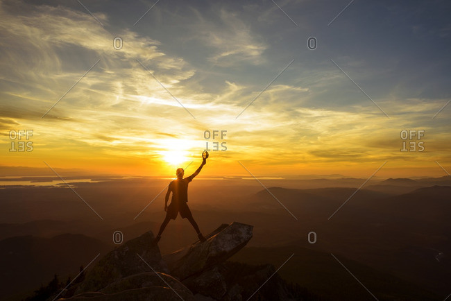 Silhouette hiker holding cap with hand raised while standing on top of mountain during sunset