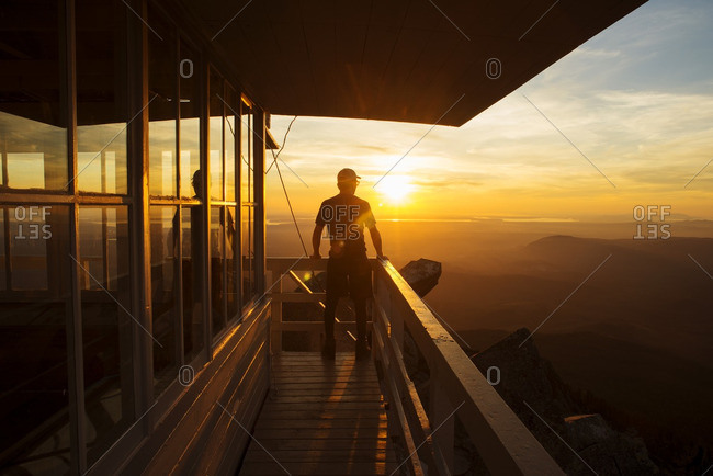 Rear view of hiker standing at fire lookout tower during sunset