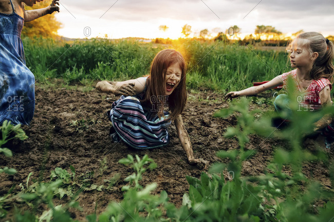 Girl with sisters shouting while crouching in mud