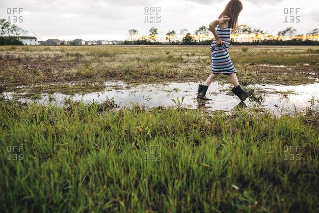 Side view of messy girl walking on wet field