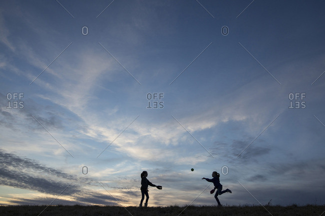 Silhouette sisters playing with ball on field against sky