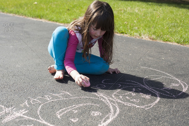 A girl drawing on asphalt with chalk