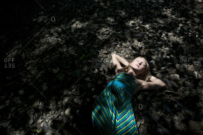 A girl lying on stones in shadows
