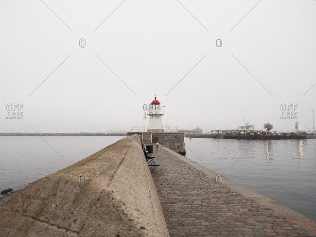 Stone pier and lighthouse in fog