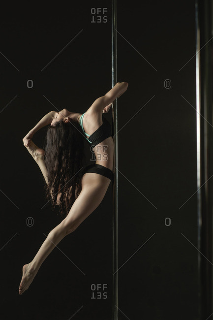 Woman pole dancing against gray background