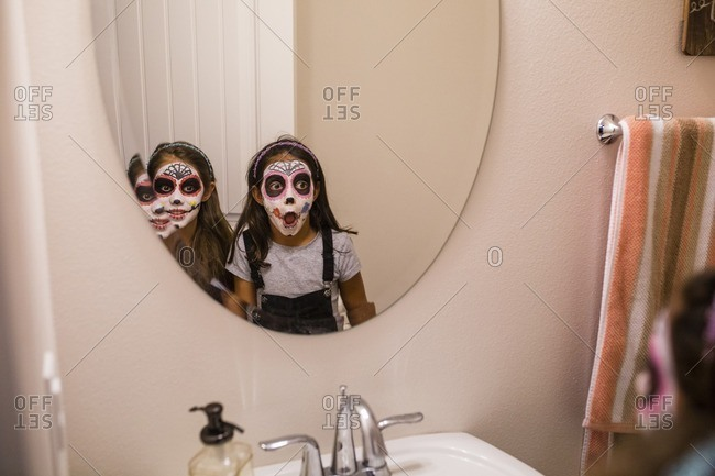 Sisters with face paint looking into mirror
