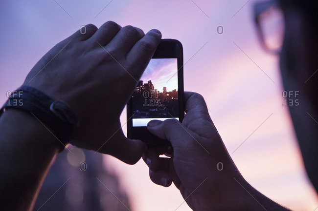 Cropped image of man photographing buildings during sunset