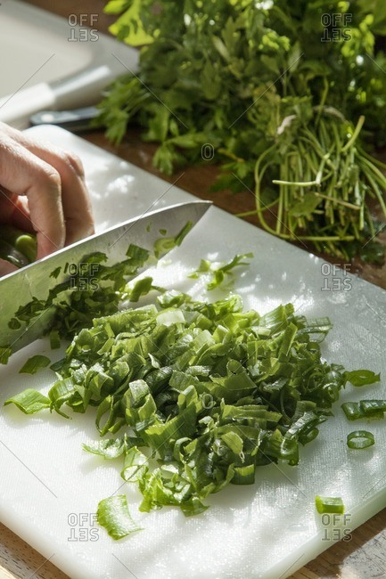 Cropped image of person chopping scallions in kitchen